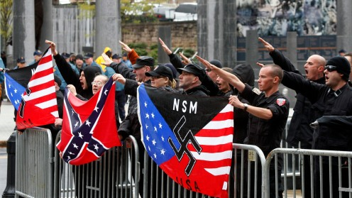 """Members of the neo-Nazi National Socialist Movement hold flags as they salute and shout """"Sieg Heil"""" during a rally in front of the Statehouse in Trenton, N.J., Saturday, April 16, 2011. (AP Photo/Mel Evans)"""